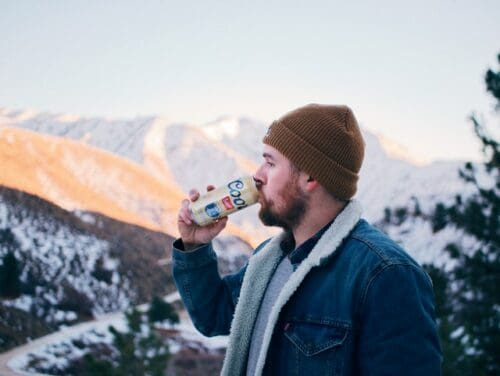 man drinking Coors in the mountains